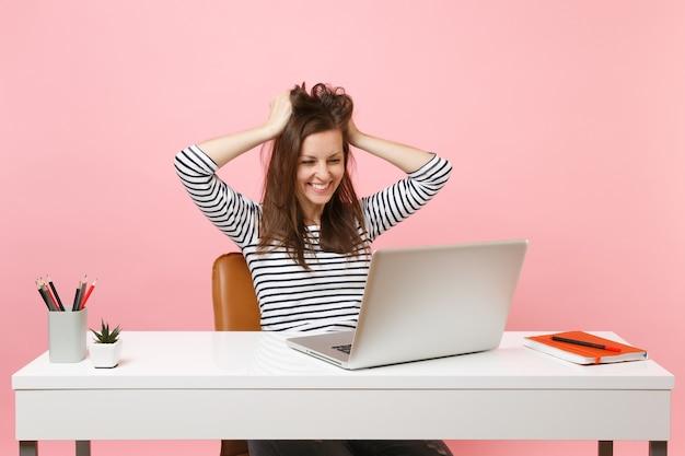 Jeune femme satisfaite s'accrochant aux cheveux, chef de finition travaillant sur un projet complet avec un ordinateur portable tout en étant assis au bureau
