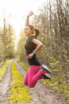 Jeune femme sautant avec un bras levé