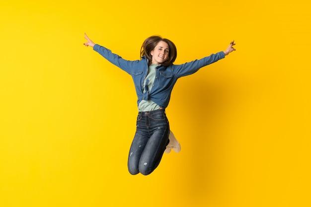 Jeune femme sautant sur fond jaune