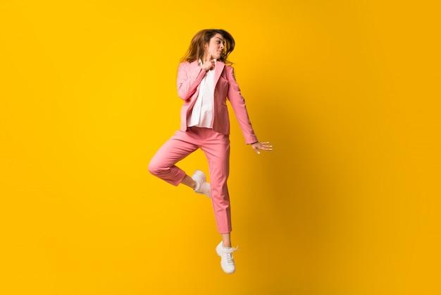 Jeune femme sautant sur un mur jaune