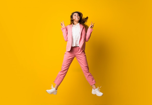 Jeune femme sautant par-dessus un mur jaune isolé