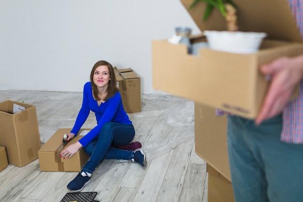 Jeune femme scellant des boîtes sur le plancher