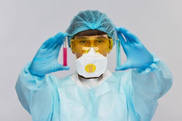 Jeune femme scientifique en chapeau médical jetable et lunettes de protection jaunes tenant des tubes à essai avec des liquides bleus et roses
