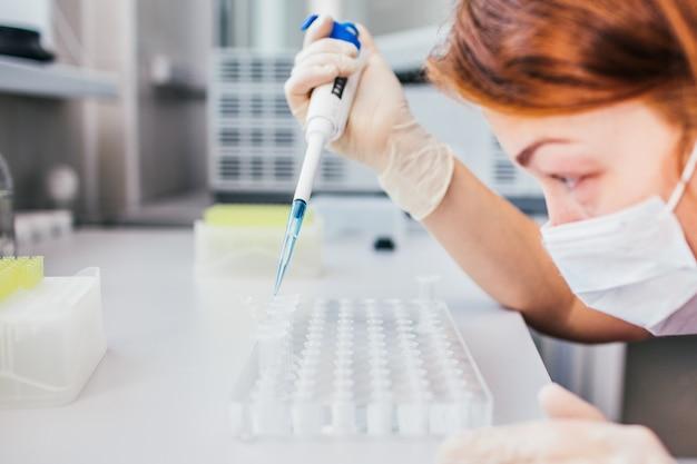 Jeune femme scientifique dans une blouse blanche et un masque travaille dans un laboratoire biologique ou médical moderne se préparant au test d'adn