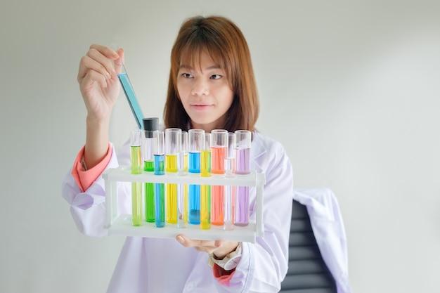 Jeune femme scientifique examinant avec tube à essai de couleur en laboratoire pour la recherche scientifique