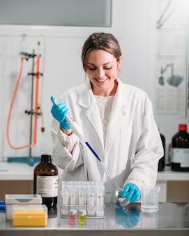 Jeune femme scientifique travaillant avec une pipette dans un laboratoire