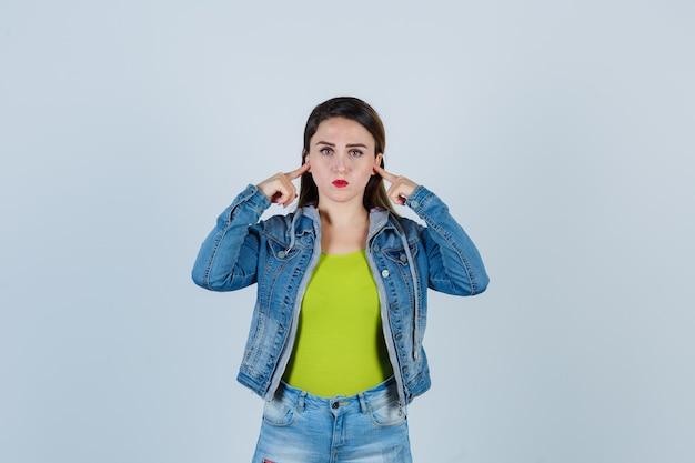Jeune femme se branchant les oreilles avec les doigts en tenue de denim et ayant l'air de s'ennuyer. vue de face.