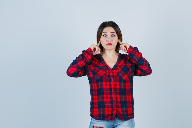 Jeune femme se branchant les oreilles avec l'index en chemise à carreaux, jeans et semblant harcelée. vue de face.