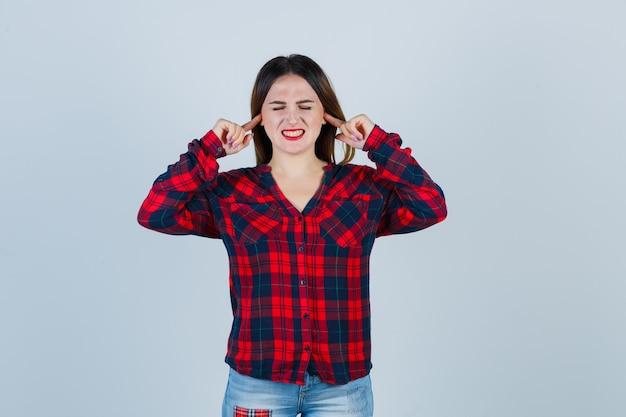 Jeune femme se branchant les oreilles avec l'index, gardant les yeux fermés dans une chemise à carreaux, un jean et l'air harcelé, vue de face.