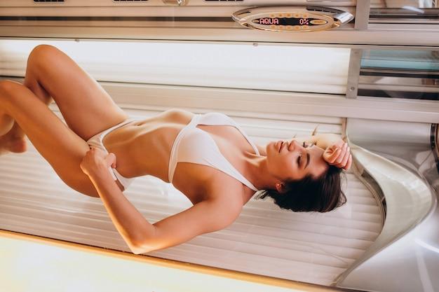 Jeune femme se bronzer au solarium