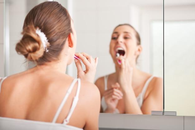 Jeune femme se brosser les dents au lavabo