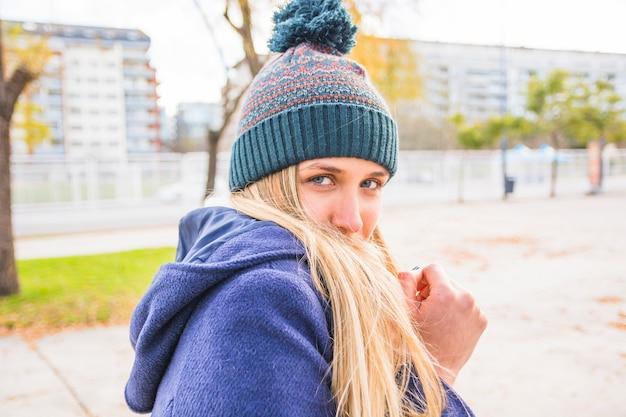 Jeune femme se cachant du vent d'automne