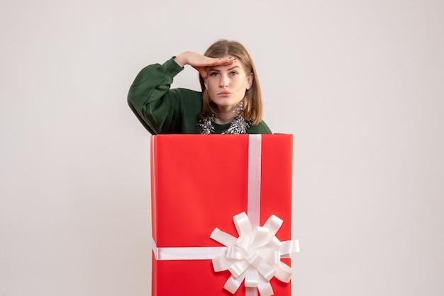 Jeune femme se cachant à l'intérieur de la boîte présente sur blanc