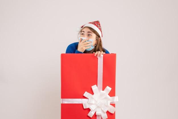 Jeune femme se cachant à l'intérieur de la boîte présente en masque sur blanc