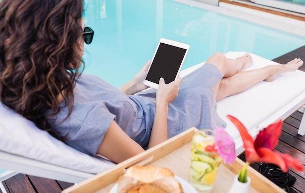 Jeune femme se détendre sur une chaise longue et à l'aide de tablette numérique près de la piscine