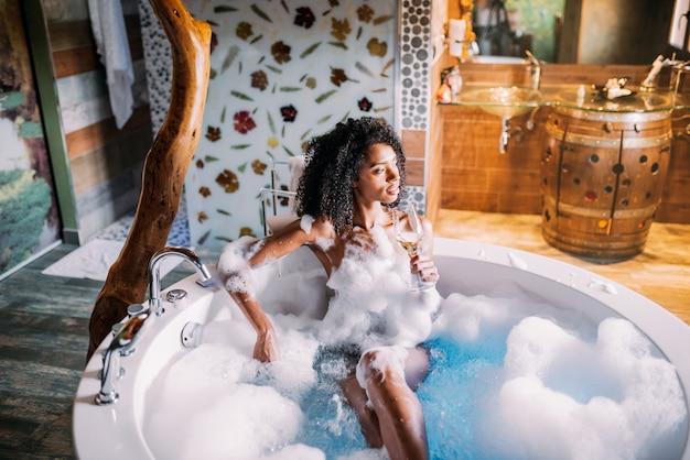 Jeune femme se détendre dans le bain d'hydromassage recouvert de mousse