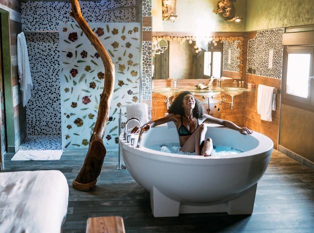 Jeune femme se détendre dans le bain d'hydromassage