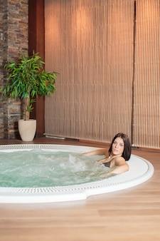 Jeune femme se détendre dans le bain à remous