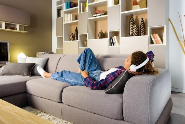 Jeune femme se détendre dans le salon ou tanière à la maison sur un canapé en écoutant de la musique sur des écouteurs stéréo