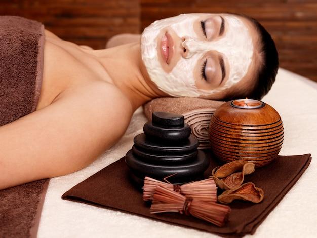 Jeune femme se détendre avec un masque cosmétique sur le visage au salon de beauté - à l'intérieur