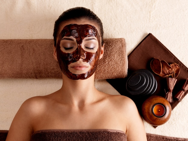 Jeune femme se détendre avec un masque facial sur le visage au salon de beauté - à l'intérieur
