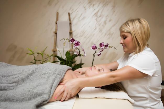 Jeune femme se détendre pendant le massage du corps de l'épaule au spa