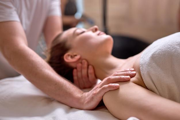 Jeune femme se détendre pendant un massage spa dans un centre de beauté