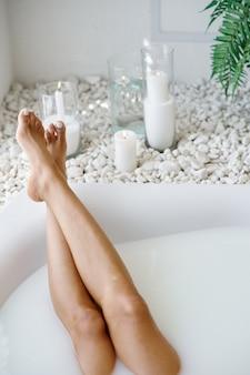 Jeune femme se détendre, soins de la peau dans le bain avec du lait. personne de sexe féminin dans la baignoire, soins de beauté et de santé au spa, traitement de bien-être dans la salle de bain, cailloux et bougies sur fond