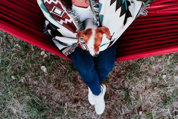 Jeune femme se détendre avec son chien dans un hamac