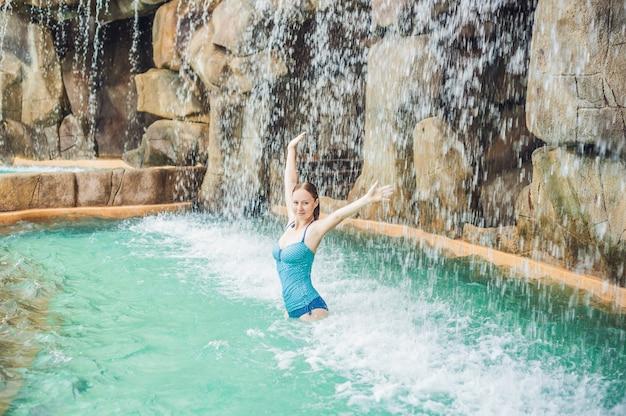 Jeune femme se détendre sous une cascade dans un parc aquatique