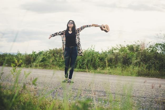 Jeune femme se détendre ukulélé brun de pentecôte dans le parc.