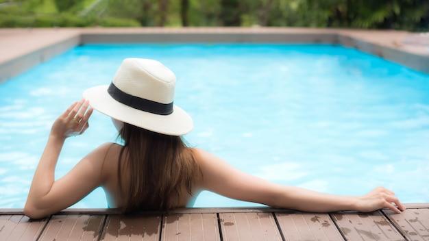 Jeune femme se faire bronzer dans la piscine de la station balnéaire du bungalow