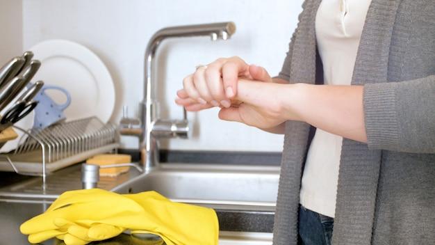 Jeune femme se frottant les mains douloureuses après avoir fait des travaux ménagers et nettoyé la cuisine.