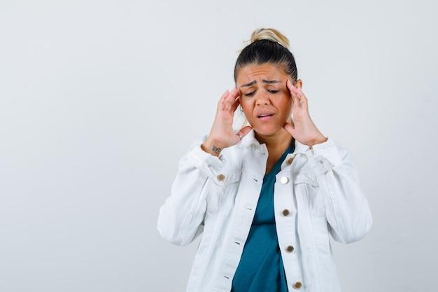 Jeune femme se frottant les tempes en chemise, veste blanche et semblant douloureuse, vue de face.