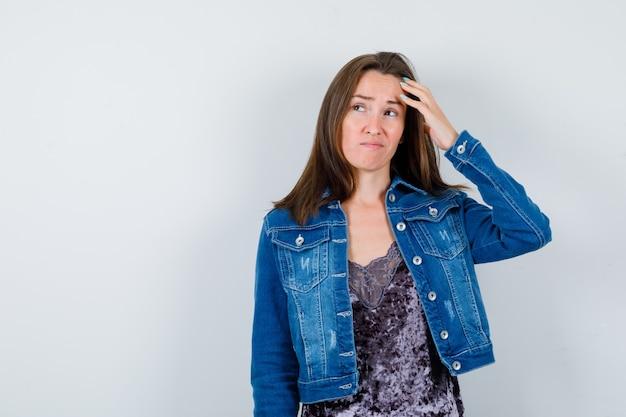 Jeune femme se grattant la tête en chemisier, veste en jean et regardant pensive. vue de face.