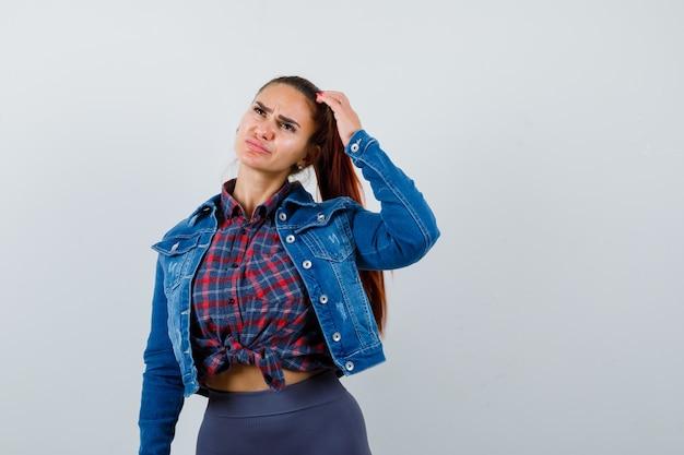 Jeune femme se grattant la tête en détournant les yeux en chemise à carreaux, veste en jean et l'air réfléchi, vue de face.
