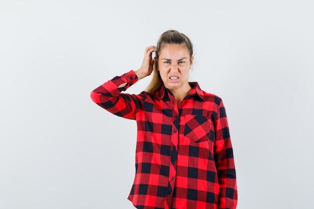 Jeune femme se gratter la tête en chemise à carreaux et regardant pensif, vue de face.