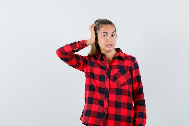 Jeune femme se gratter la tête en chemise à carreaux et à la vue troublée, de face.