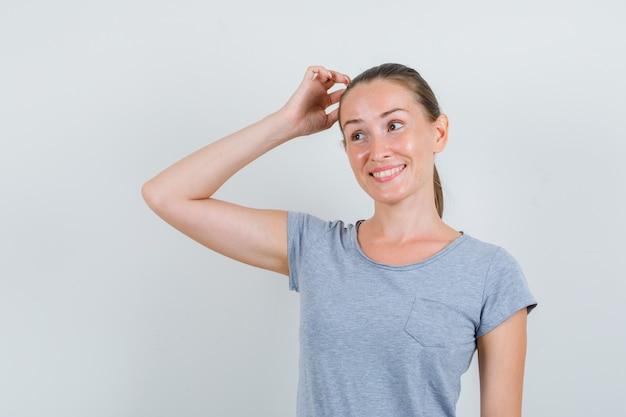 Jeune femme se gratter la tête en t-shirt gris et à hésiter. vue de face.