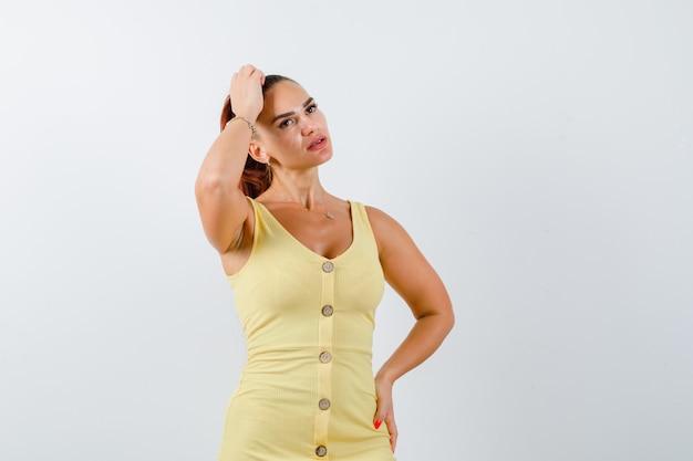 Jeune femme se gratter la tête tout en regardant en robe jaune et à la réflexion. vue de face.