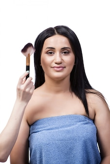 Jeune femme se maquillage isolé sur blanc