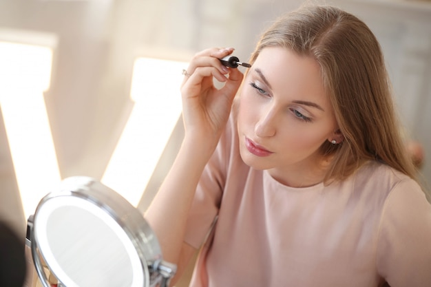 Jeune femme se maquiller.