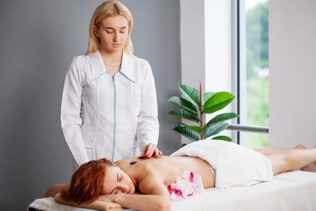 Jeune femme se massage aux pierres chaudes dans le salon spa.