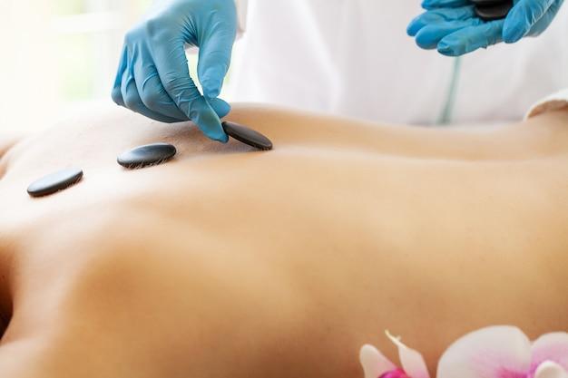 Jeune femme se massage aux pierres chaudes dans le salon de spa.
