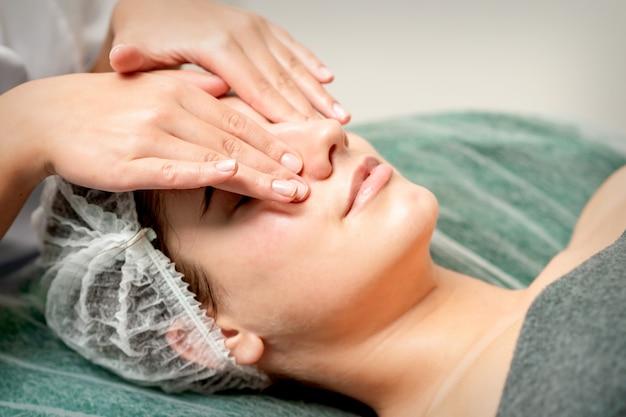 Jeune femme se massage du visage avec les yeux fermés par esthéticienne dans un salon de beauté