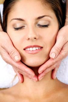 Jeune femme se massage du visage
