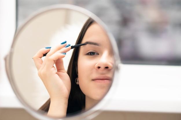 Une jeune femme se peigne les sourcils avec une brosse en se regardant dans le miroir