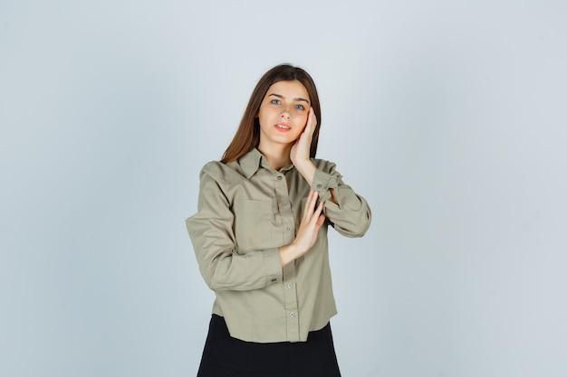 Jeune femme se penchant la joue sur la paume en chemise, jupe et à la gaieté, vue de face.