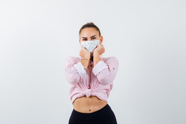 Jeune femme se penchant le menton sur les poings en chemise, pantalon, masque médical et à la jolie vue de face.