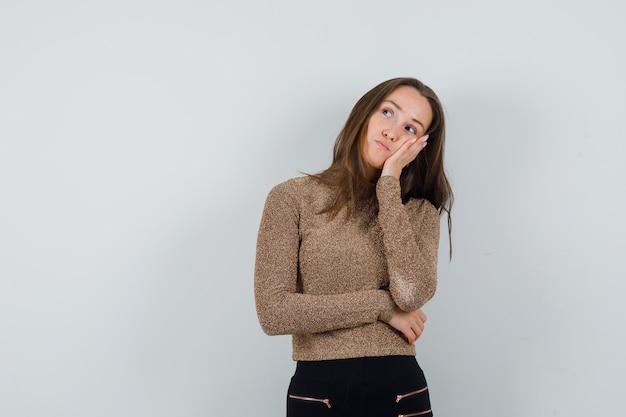Jeune femme se penchant à sa main en chemisier doré et à l'ennui